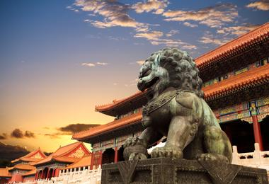 A statue of a lion guards the entrance to the Forbidden City in Beijing