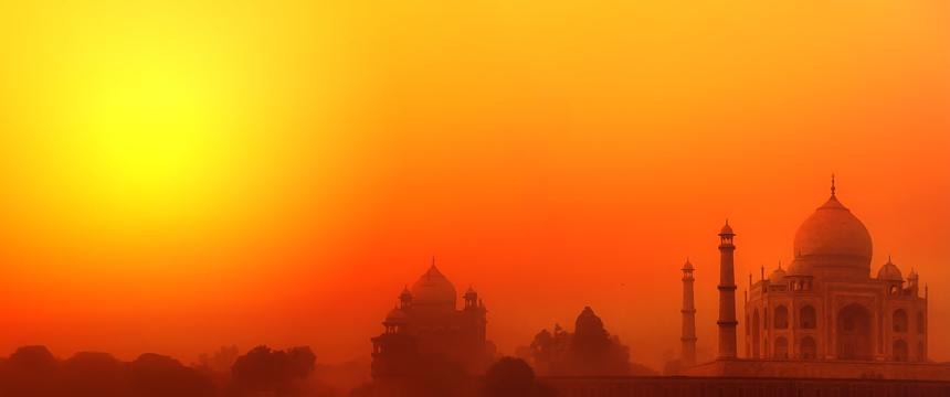 The sun sets of the Taj Mahal with an orange glow